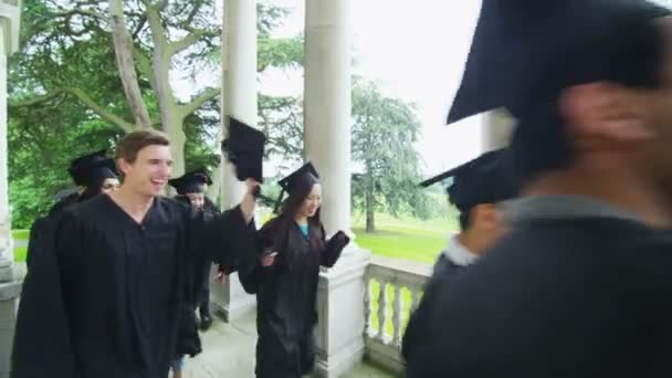 Students on graduation day run down staircase
