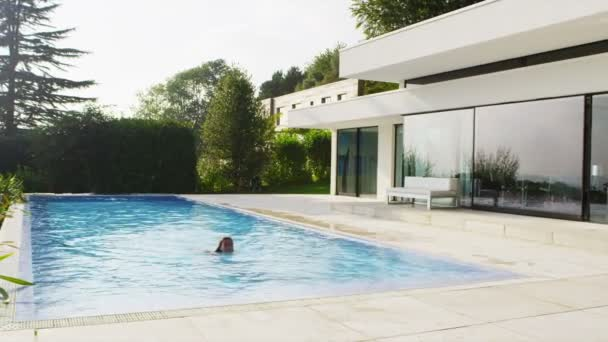 Woman swimming, steps out of pool