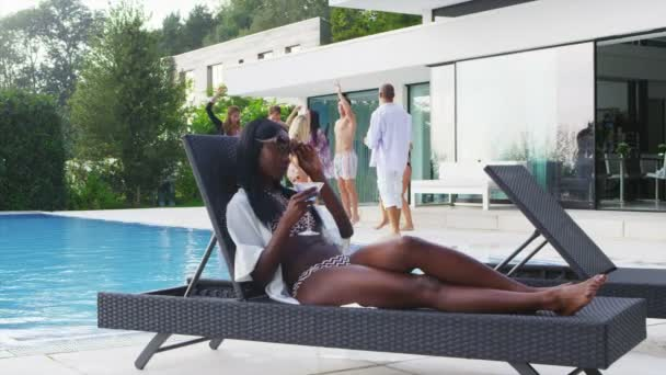 Woman drinking cocktail by pool
