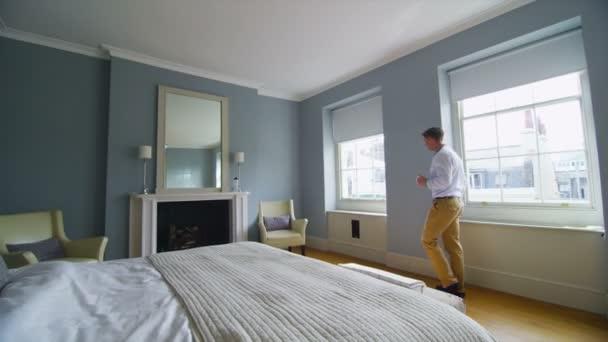 uomo in camera da letto elegante sta dalla finestra