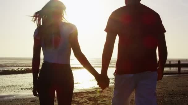 Couple holding hands and walking on beach