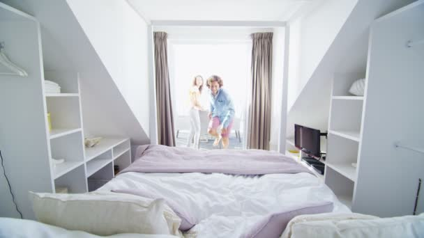 Couple run to jump on bed