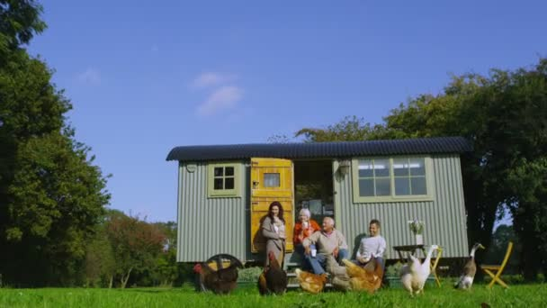 Family outside caravan with chickens and ducks