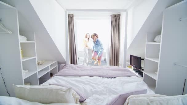paar ausführen, auf dem Bett zu springen