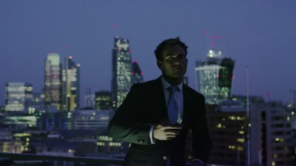 Successful businessman looks out at the view of the London city skyline at night