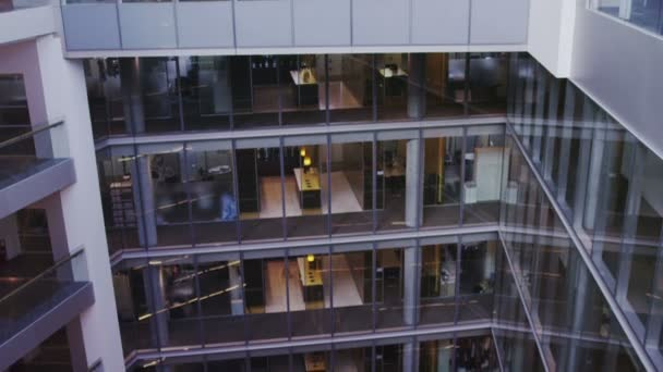 Interior view of modern office building with glass partitions and central atrium