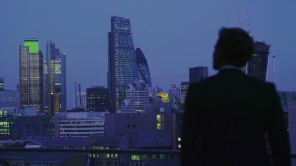 imprenditore di successo si affaccia la vista della skyline di città di Londra di notte
