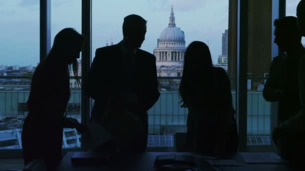 Business group in silhouette shake hands at the end of a meeting