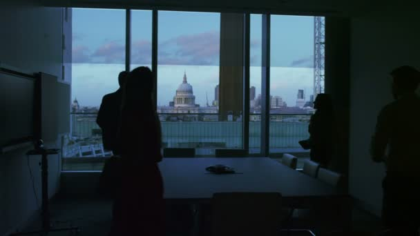 Business group in silhouette sit down for a meeting in a London city office