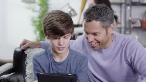 un padre e un figlio sta navigando internet su una tavoletta digitale