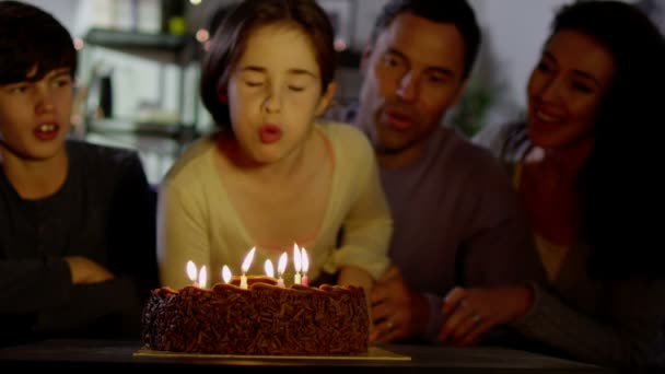 Girl blows out candles on birthday cake