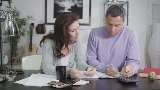 atraktivní pár sednout do práce, jejich domácími účty