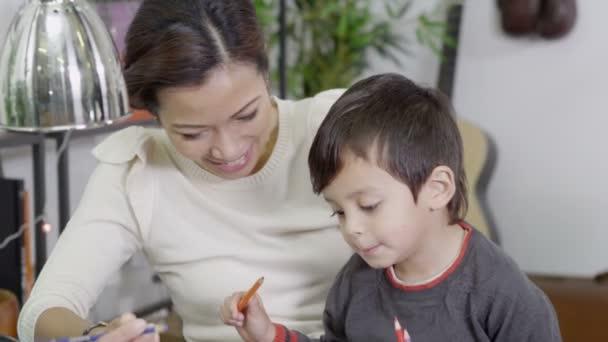 madre e figlio di disegno e scrittura con matite colorate