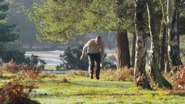 Man running with dog through forest