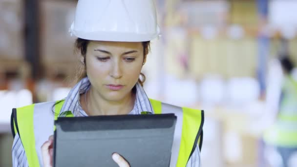 Female warehouse employee is working on tablet