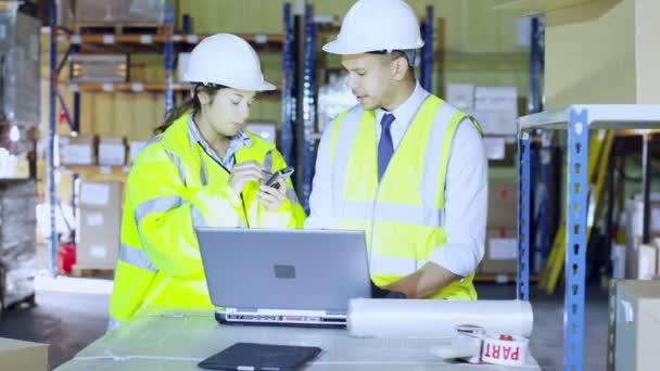 dva pracovníci skladu diskutovat o logistické společnosti