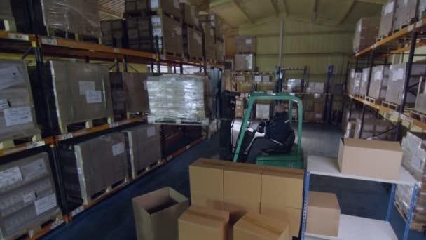 pracovník používá vysokozdvižný vozík přesunutí komíny krabic