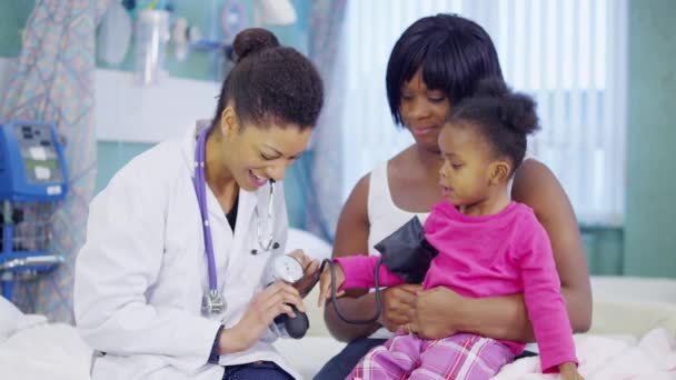 Female doctor checking the blood pressure of a cute little girl in hospital