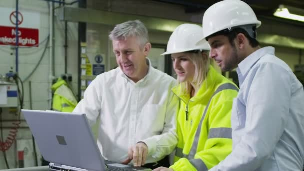 Three workers in a warehouse with a laptop are discussing their work.