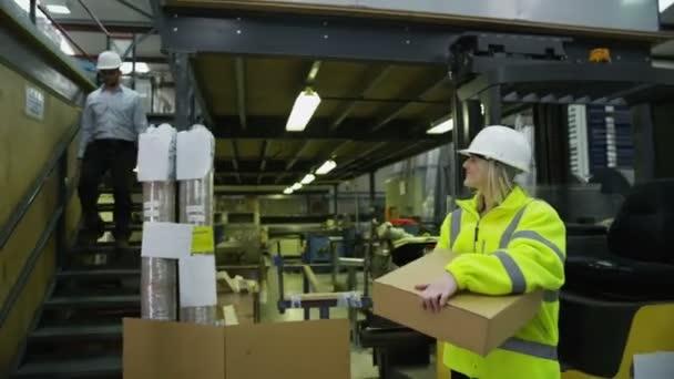 pracovníci ve skladu s přenosným počítačem se připravují zboží k dodání