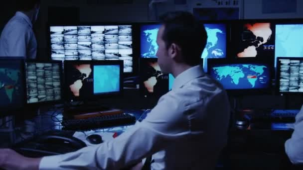 Security personnel working in system control room.