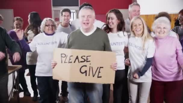 Velká skupina charita dobrovolníky úsměv do kamery drží ceduli Dejte prosím