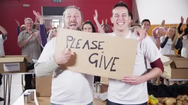 dva pracovníci charity Počkejte prosím dát znamení, jako jejich spolupracovníci tleskat