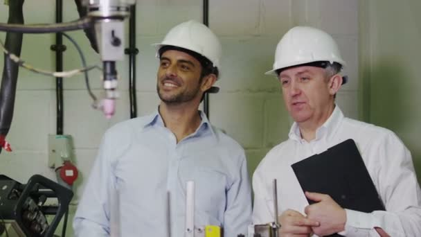 Mature male factory manager explains to younger man how the machinery works