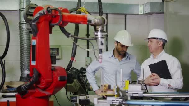 zralý muž továrny správce vysvětluje mladší muže, jak funguje strojního zařízení