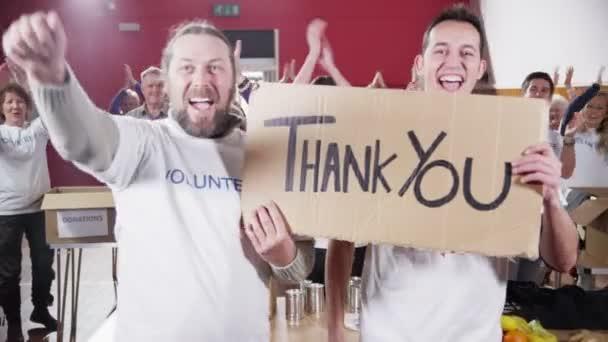 dva pracovníci charity držet Děkuji podepsat jako jejich spolupracovníci tleskat