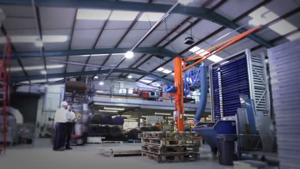 Busy warehouse workers lifting and moving empty pallets
