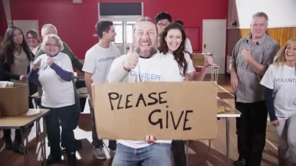 Skupina dobrovolníků charitativní dávám palec do fotoaparát s prosím dát znamení