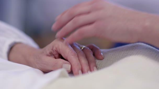 drží ruku pacienta v nemocniční posteli