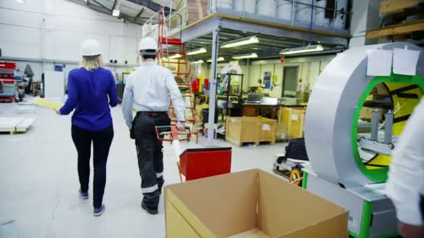 Veselá sklad mužských a ženských nebo továrních dělníků používají nosné zařízení