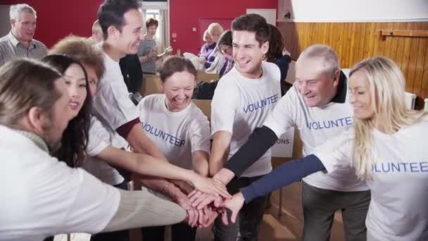 šťastné kruh dobrovolníků dali ruce v show jednoty