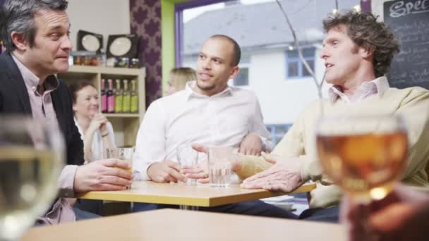 Three cheerful casual businessmen chatting together in a small cafe or wine bar
