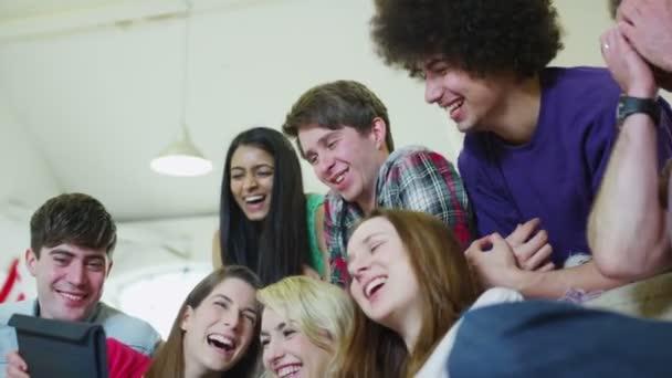 felici casuali giovani amici ridendo di ciò che vedono su un tablet PC