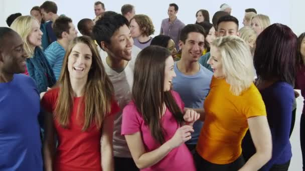 Multi ethnic group of people standing together in brightly colored casual clothing and having fun