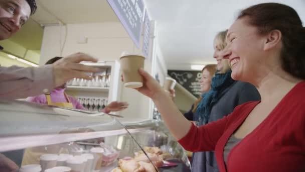barátságos férfi és női baristas kiszolgálása egy kávézóban