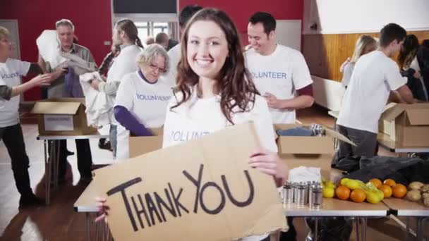 Beautiful female charity worker holds up a Thank you sign to camera