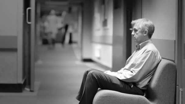 aggódik az ember ül a kórházi váró terület