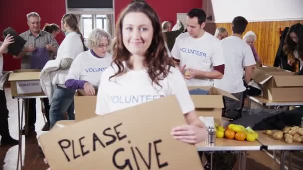 Beautiful female charity worker holds up a Please Give sign to camera