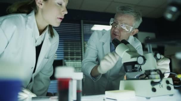 Mature male scientist teaching female student
