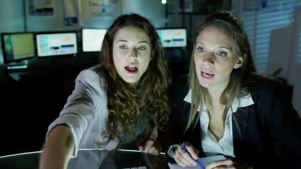 Two beautiful business women working late into the night