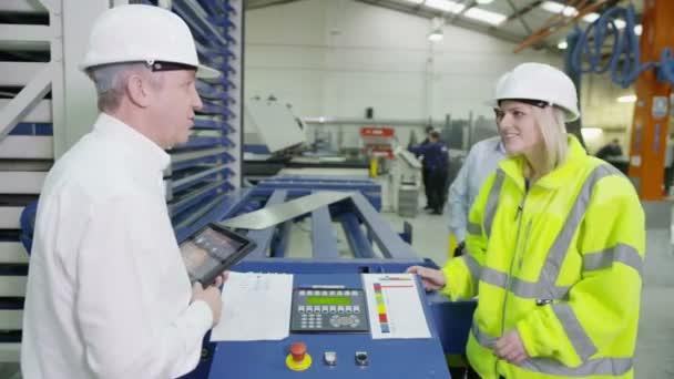 Mature factory manager shows his staff how to operate machinery