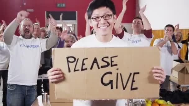 charitativní pracovník drží prosím dát znamení, jako jeho spolupracovníci tleskat