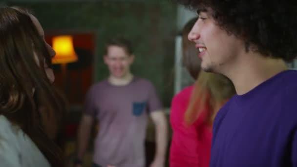 bezstarostné skupina mladých přátel, tančí a flirtuje společně na house party
