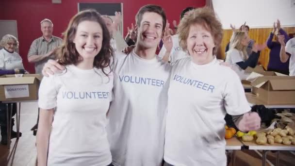 tři pracovníci charity objetí a úsměv do kamery, jako jejich spolupracovníci tleskat