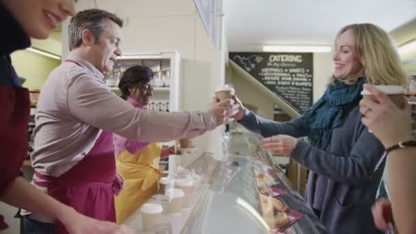 vänliga manliga och kvinnliga baristor som betjänar kunder i ett kafépřátelské mužské a ženské baristas slouží zákazníkům v kavárně