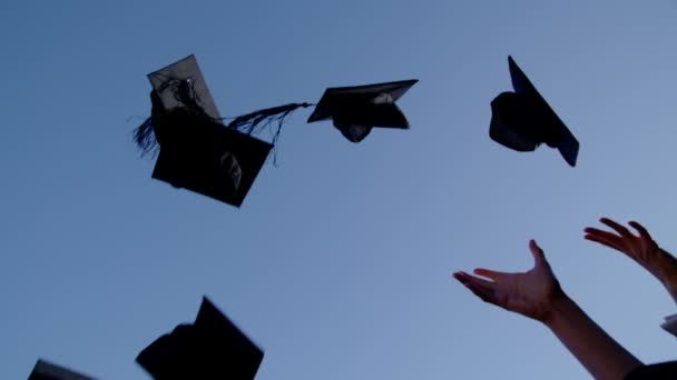Graduation caps are tossed into air